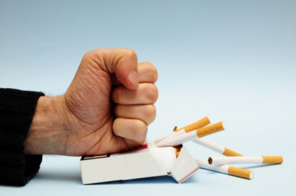 A fist crushing a pack of cigarettes because you are going to quit smoking with hypnotherapy