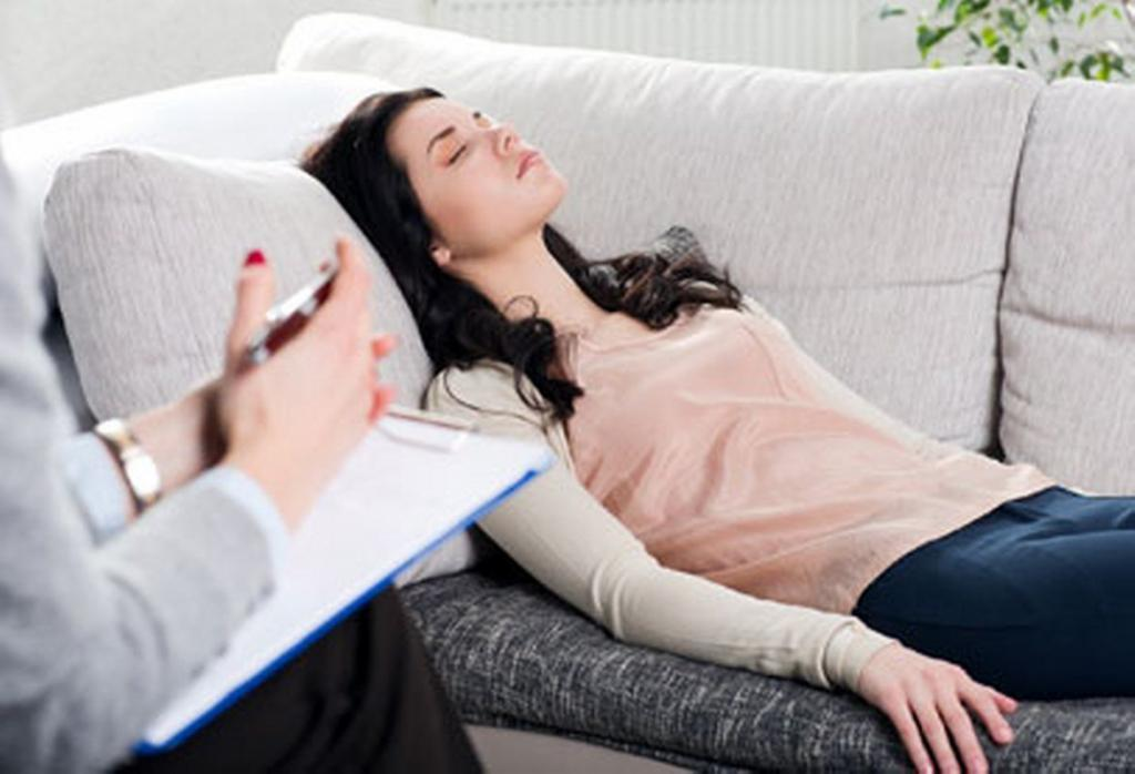 A woman laying on the sofa experiencing what does hypnosis feel like