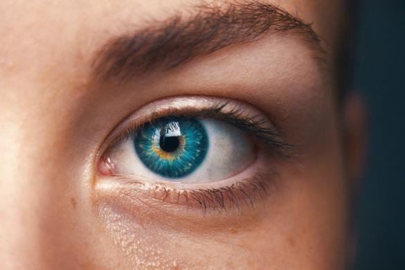 A woman's blue eye that is used to illustrate the difference between EMDR and IEMT