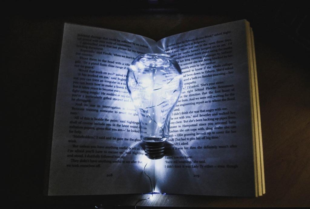 An open book with a lightbulb in the middle illustrating how to train the power of your subconscious mind