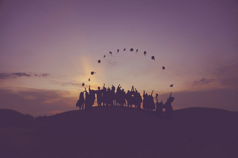 A group of graduates throwing their hat in the air on top of a mountain