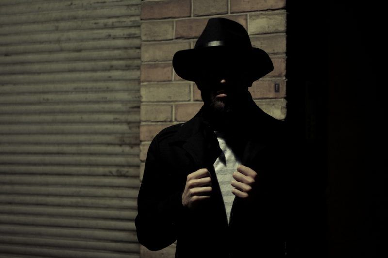 A man in a dark corner dressed as a spy in the form of a self-made alter ego personality