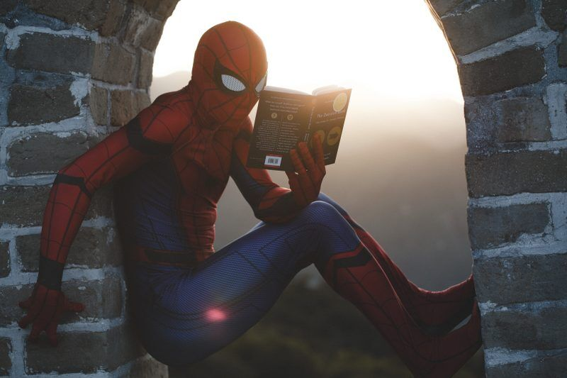 A man in a spider man suit holding a book creating and triggering his own alter ego personality