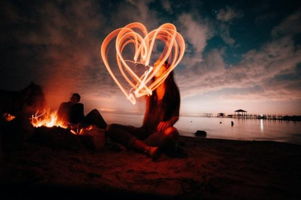 A woman sitting at the beach at night to figure out how to love and accept yourself unconditionally