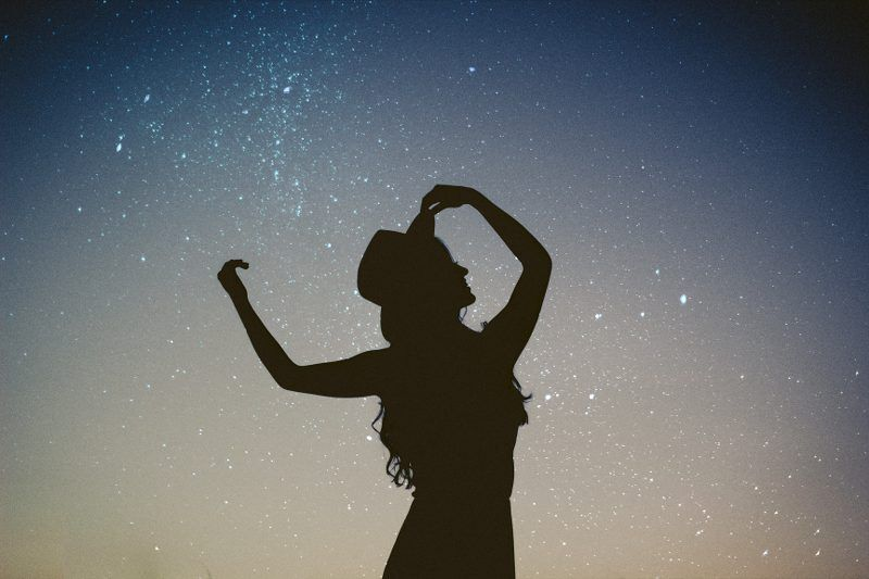 The silhouette of a woman with stars in the background