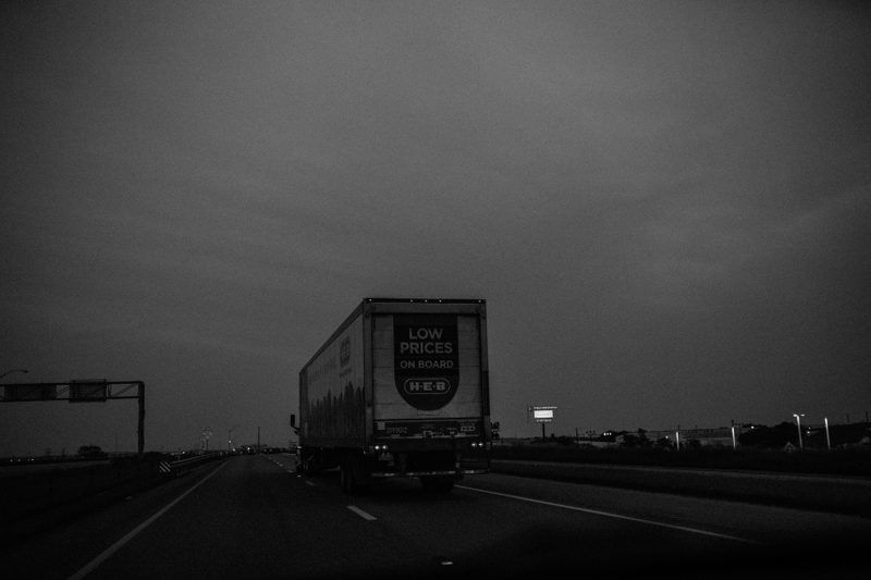 A gray picture of a truck on a highway.
