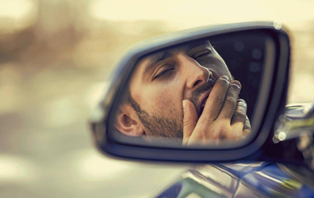 A man yawning and slowly falling asleep behind the wheel.