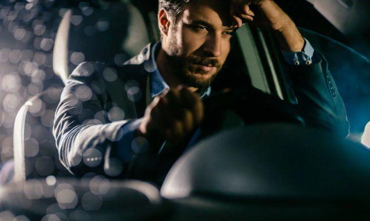 A man behind the wheel close to falling asleep.